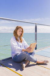 Portrait of young woman using digital tablet in front of the sea - BOYF000297