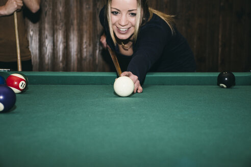 Woman playing pool billard in a bar, smiling - ABZF000382