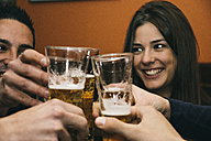 Friends toasting with glasses of beer in a bar - ABZF000391