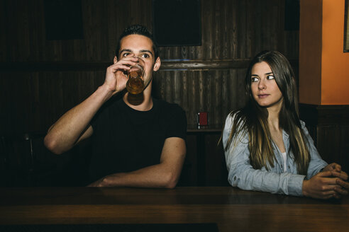 Man drinking beer at the bar counter while woman looks at him - ABZF000400
