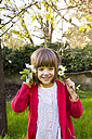 Portrait of smiling little girl holding twig of blossoming tree - LVF004824