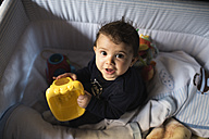 Portrait of baby boy playing in cot - JASF000706