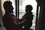 Silhouette of father holding his baby boy in front of the window - JASF000709