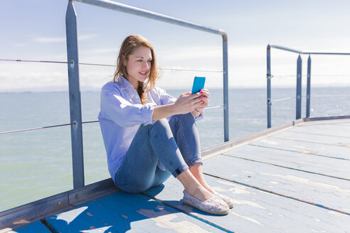 Italy, Lignano Sabbiadoro, woman sitting with smartphone on jetty - BOYF000310