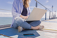 Young woman with laptop and smartphone, sitting on jetty - BOYF000325