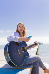 Young woman with smartphone and guitar sitting on jetty - BOYF000334