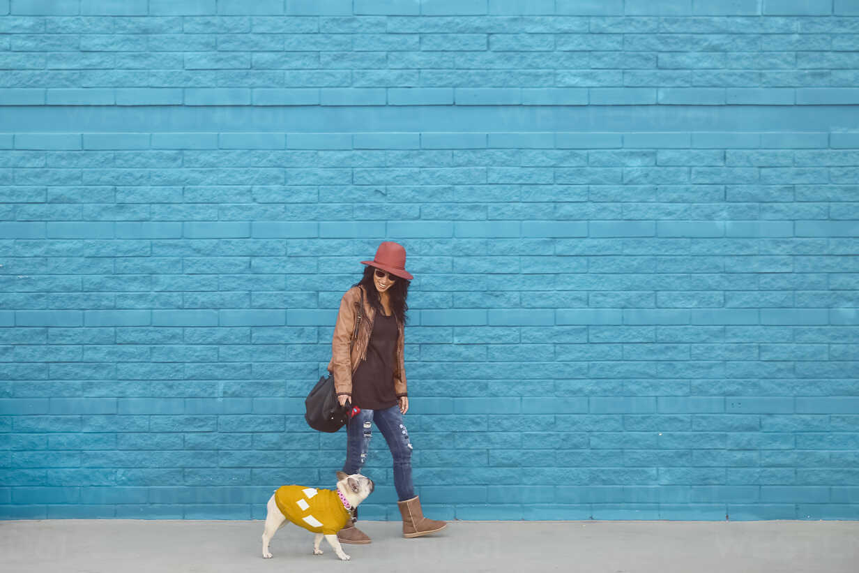 Woman going walkies with her French bulldog in front of blue wall - RTBF000168 - Retales Botijero/Westend61