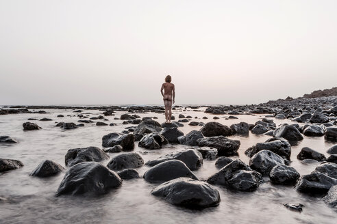 Lanzarote, Rear view of nude man standing on Playa de Janubio - WV000768