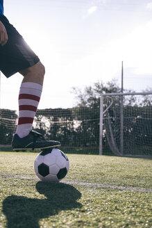 Legs of football player with ball on football ground - ABZF000449