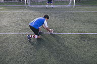 Football player placing the ball on the line in front of the goal - ABZF000452