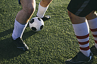 Legs of football players on football ground - ABZF000464