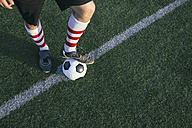 Legs of football player with ball on football ground - ABZF000467