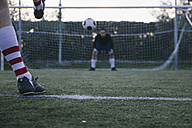 Legs of a footnball player kicking a ball in front of a goal with a goalkeeper - ABZF000476