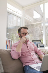 Mature man on couch drinking coffee and using laptop - BOYF000343