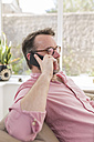 Mature man sitting on couch talking on the phone - BOYF000346