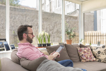 Mature man sitting on couch using digital tablet - BOYF000349