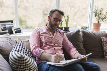 Mature man sitting on couch marking advertisments in newspaper - BOYF000358