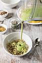 Smoothie bowl with lineseed, sunflower seeds and nuts, pouring smoothie - EVGF002929