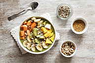 Smoothie bowl with different fruits, mango, papaya, kiwi, banana and pear and toppings, lineseeds, sunflower-seeds and nuts - EVGF002932