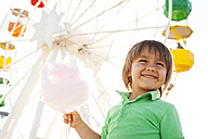 Portrait of happy little boy with cotton candy in front of big wheel - VABF000480