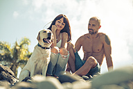 Couple sitting with their dog on stony beach - SIPF000419