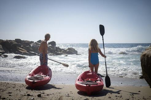 Senior couple pushing canoes by the sea - ABAF002008