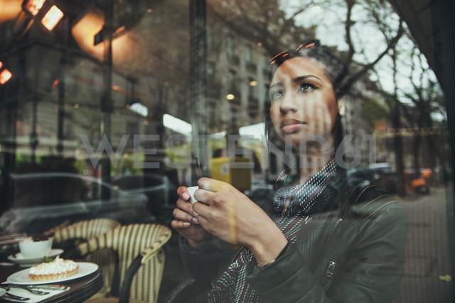 Pensivef young woman sitting behind windowpane of a cafe - ZEDF000088