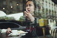 Young woman sitting behind windowpane of a cafe eating cake - ZEDF000091