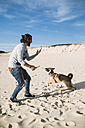 Man playing with his mongrel on the beach - RAEF001141