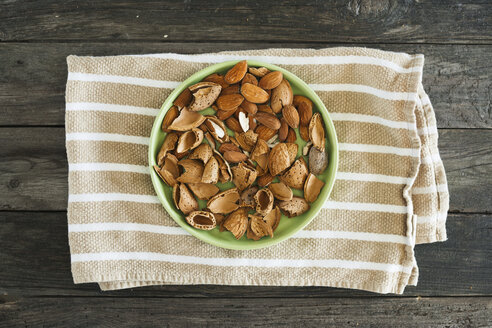 Almonds, green plate, kitchen towel on wood - JPF000138