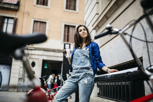 Spain, Barcelona, young woman with a coffee in the city - JRFF000614