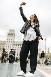 Spain, Barcelona, young woman taking a selfie in the city - JRFF000617