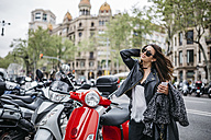 Spain, Barcelona, young woman in the city next to parked motor scooters - JRFF000620