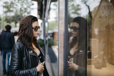 Young woman in the city looking at shop window - JRFF000623
