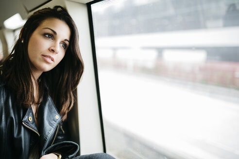 Young woman on train looking out of window - JRFF000629