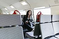 Young woman on train looking out of window - JRFF000632