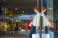 Young woman with cell phone and shopping bags - DIGF000401