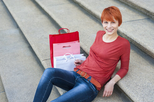 Smiling young woman sitting on stairs with shopping bags next to her - DIGF000419