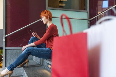 Young woman sitting on stairs with cell phone and shopping bags next to her - DIGF000425