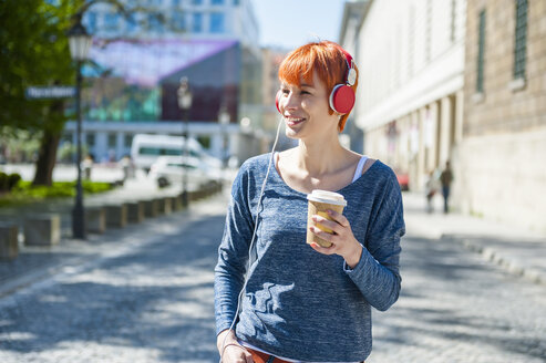 Smiling young woman with coffee to go listening to music - DIGF000449