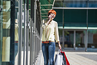Happy young woman with shopping bags on cell phone - DIGF000461