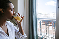 Young woman drinking glass of juice while looking through window - ZEDF000095