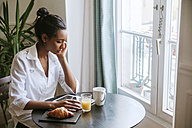 Young woman using digital tablet at breakfast table - ZEDF000101
