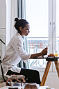Young woman using digital tablet at breakfast table - ZEDF000104