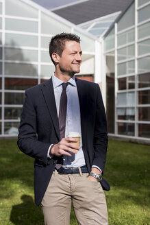 Smiling businessman outdoors with coffee to go - MAUF000513