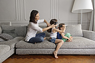 Mother and her children sitting in a row on the couch combing their hair with hairbrushes - LITF000273