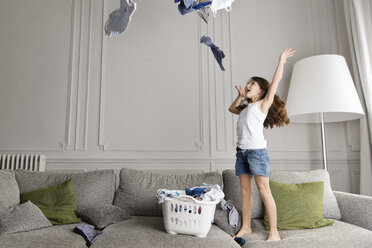Little girl standing on the couch throwing laundry in the air - LITF000276