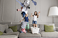 Siblings standing on the couch throwing laundry in the air - LITF000279
