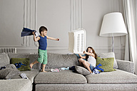 Little boy standing on the couch fighting with laundry while his sister protecting herself with laundry basket - LITF000282