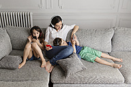 Mother and her children sitting on the couch listening music with their headphones and smartphones - LITF000285